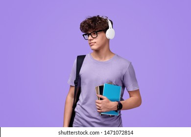 Teen hipster with notebooks and backpack looking away while listening to music in headphones before studies against purple background