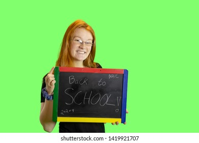 Teen holding blackboard with back to school isolated on green with copy space.