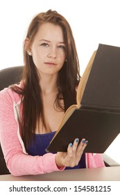 A teen is holding a book sideways with a confused look.