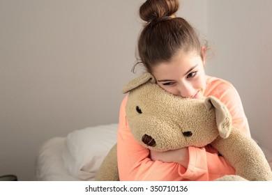 teen hugging her teddy bear in her room
