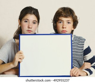 teen kids boy and girl hold blank paper sheet in frame close up portrait