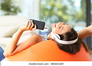 Teen listening music with headphones and smart phone lying on an orange pouf in the living room at home
