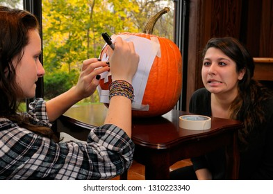Teen making a face while her friend draws a stencil onto a pumpking for Halloween