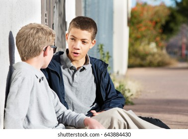 Teen male talking to friend seated outside on ground
