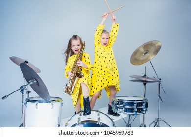 Teen music girls performing in a recording studio. The group of two girls standing together. Studio portrait of young attractive fashion caucasian teen girls. Kids fashion and rock music concept