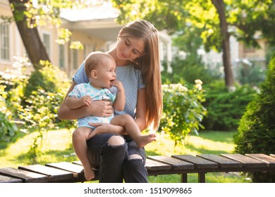 Teen nanny with cute baby outdoors on sunny day
