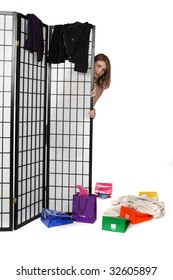 teen peeking from behind a screen with shopping bags and clothes strewn about