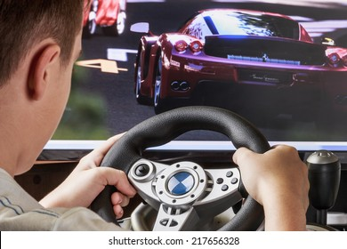 Teen playing in the race behind the wheel of a game console