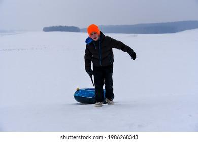 Teen Pulls Tubing Down A Snow Slide.