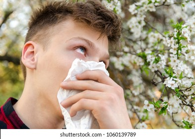 Teen with red eyes having allergic reaction to tree pollen