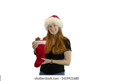 Teen in red and white Christmas hat holding stocking filled with wrapped gifts isolated on white with copy space.