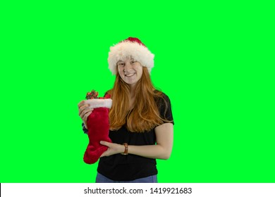 Teen in red and white Christmas hat holding stocking filled with wrapped gifts isolated on green with copy space.