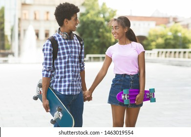 Teen Romance Concept. Happy teenage couple with modern skateboards holding hands walking along city street. Free space
