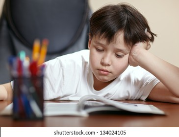 A teen school boy studies hard over his book at home as he props his head up with his arm.