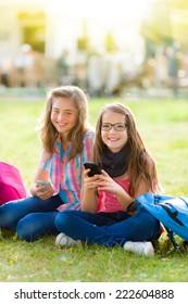 Teen schoolgirls having fun with mobile phone in the park