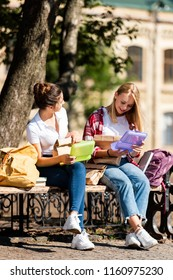 teen schoolgirls sitting on bench with lunch boxes