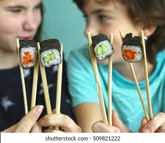 teen siblings boy and girl kids with sushi rolls avocado and salmon close up smiling photo
