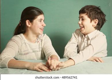 teen siblings boy and girl srtugglig arm wrestling close up photo