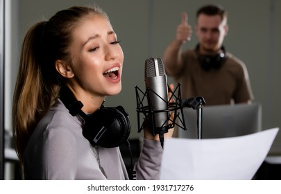 Teen singer working in vocal recording studio with happiness and concentration and male sound engineer team control and support her in blur background.