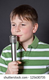Teen singing into a microphone on a black background