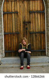 Teen  sitting on church steps.