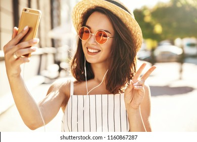 Teen smiling girl in summer white hipster clothes in headphones taking selfie on smartphone on warm sunset background in the street
