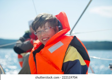 Teen smiling while wearing a life jacket with sea in the background.