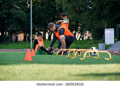 Der Teenagerfußspieler verletzte sich während des Trainings am Bein. Kinder Verletzungen im Sportkonzept. Trainer hilft seinem Schüler nach dem Unfall.