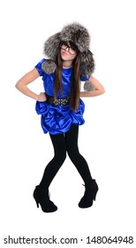 teen is standing in strict pose. Blue dress, glasses, fur hat.