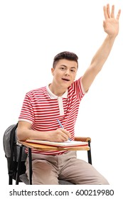 Teen student sitting in a chair and raising his hand isolated on white background