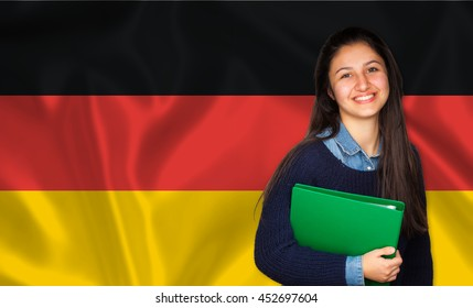Teen student smiling over german flag. Concept of lessons and learning of foreign languages.