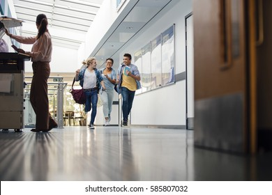 Teen students are running down the hall of their school with bags and books in their hands. There is a teacher at the printer and she is turning to look at them.