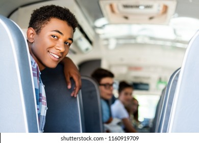 teen students sitting at school bus and looking back at camera