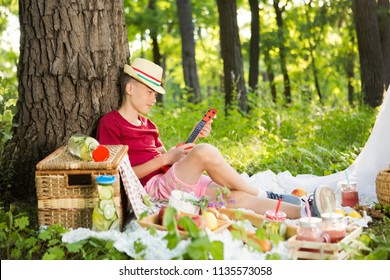 Teen stylish boy resting and eating in park on picnic. Happiness summer weekend concept.