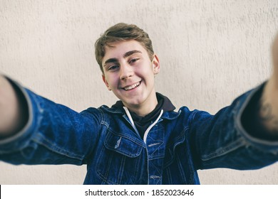 Teen takes a selfie - young man takes pictures of himself - happy teen takes pictures of himself on his phone and smiles at the camera