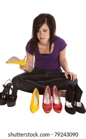 A teen is trying to figure out which pair of shoes to wear.