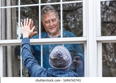 Teen visiting senior citizen quarantined in home, touching hands through the window