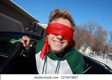 Teen wearing a blindfold getting out of a car ready for a challenge