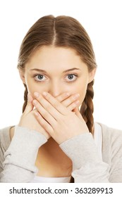 Teen woman covering her mouth.
