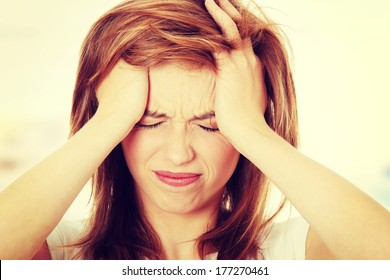 Teen woman with headache holding her hand to the head