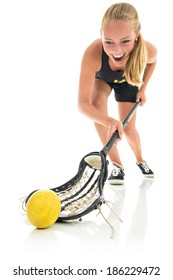 Teen woman playing lacrosse. Exaggerated wide angle on foreground where she scoops up the ball. Studio shot, with white background and reflective floor.