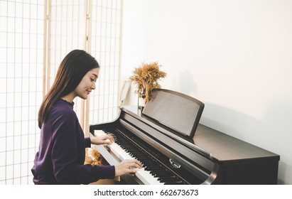 Teen Woman playing the piano.  Yong player musical for lifestyle concept.
