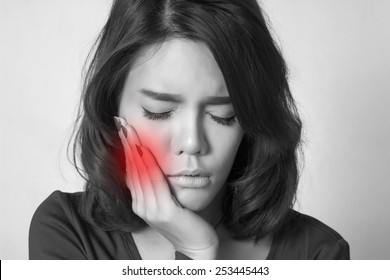 Teen woman pressing her bruised cheek with a painful expression as if she's having a terrible toothache.