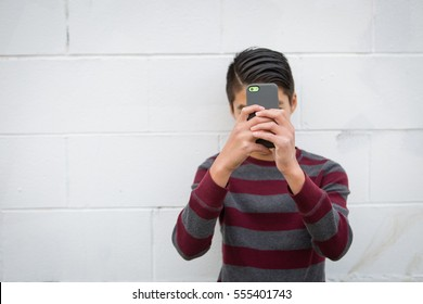 Teenage Asian boy standing alone against an urban, white, outdoor background, holding his smartphone up to obscure his face. Teen social concepts: Lost in social media, addicted to social media