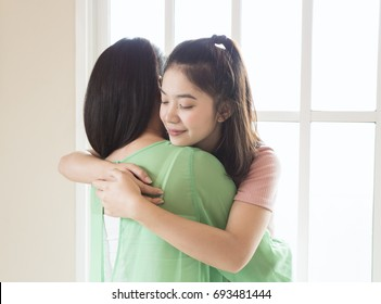 Teenage asian girl hugging her mother in living room with window light, love and care mom concepts.