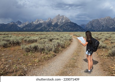 A teenage Asian girl reading a map in the Grand Teton National Park, Wyoming, USA