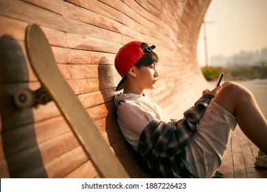 teenage asian skateboarder boy looking at cellphone while resting