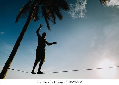 teenage balancing on slackline with sky view on the beach silhouette