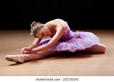 Teenage ballerina performing stretching exercises and warming up