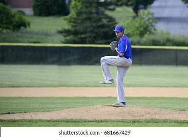 Teenage baseball pitcher on the pitching mound winding up to throw